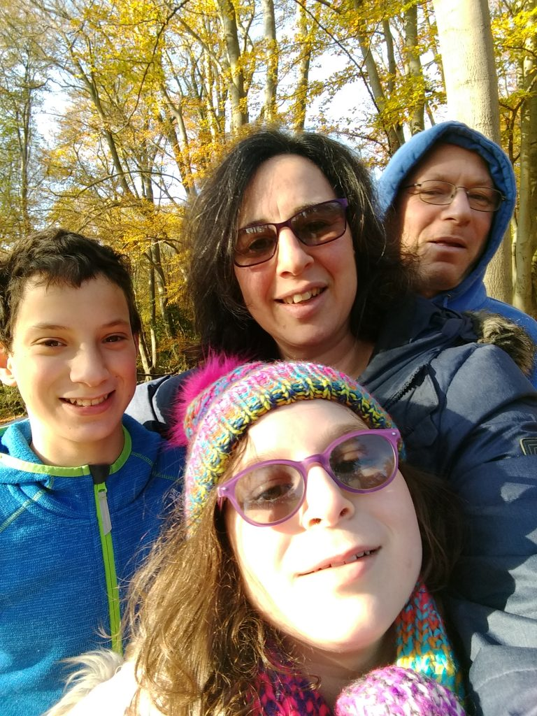 An image of David Bara with his family; Wife Emma and children, Asher and Adi. It is a selfie taken on a walk in the woods.