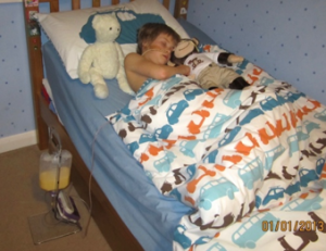 A young Sam in bed with an NG tube and the apparatus next to the bed that feeds him overnight. He is cuddled up to his toy monkey.