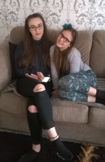 An image of Caroline Bailey's daughters - two teenage, smiling and sitting together on a sofa.