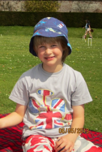 A smiling Sam, sitting on the grass, there is no NG tube. His cheeks are rosy and filled out.