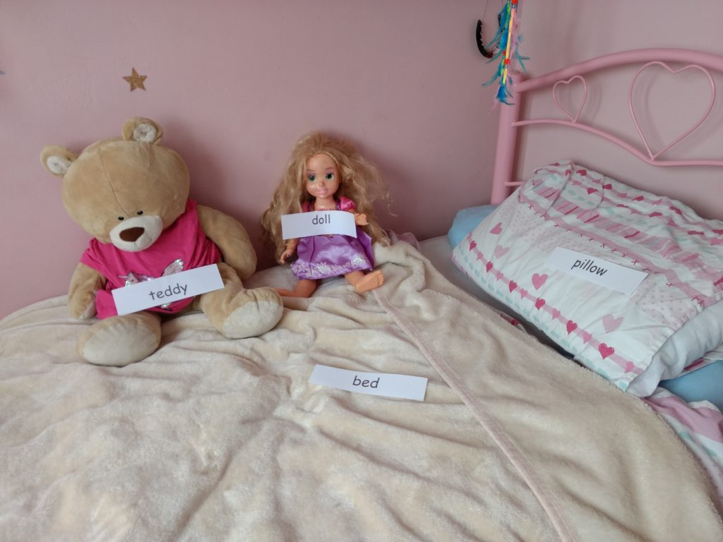 an image of a bed with a teddy and a doll on it. There are labels saying teddy, doll, bed and pillow on those items on the bed.