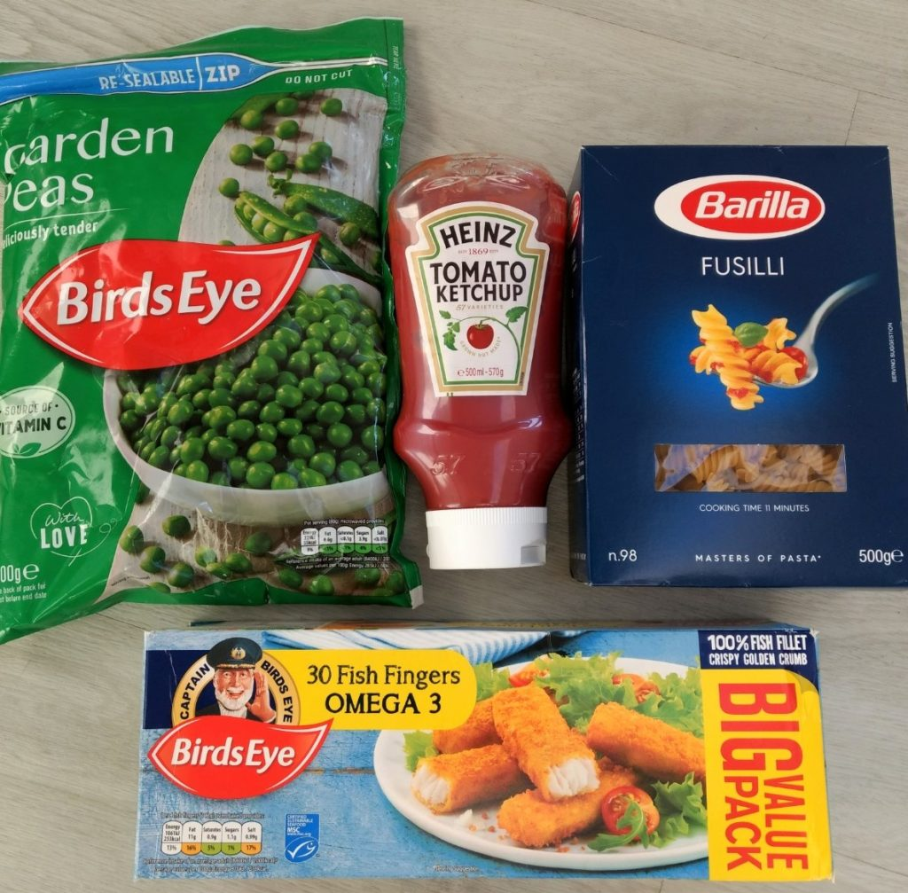 image showing a packet of frozen peas, fish fingers, pasta and tomato ketchup.