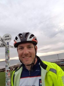 head shot of Tom in his cycling gear, next to the John O'Groats signpost.