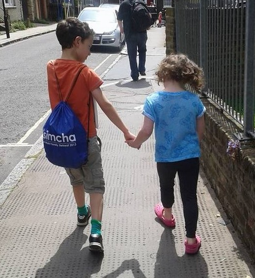 Image of a young boy and girl from behind walking hand in hand.