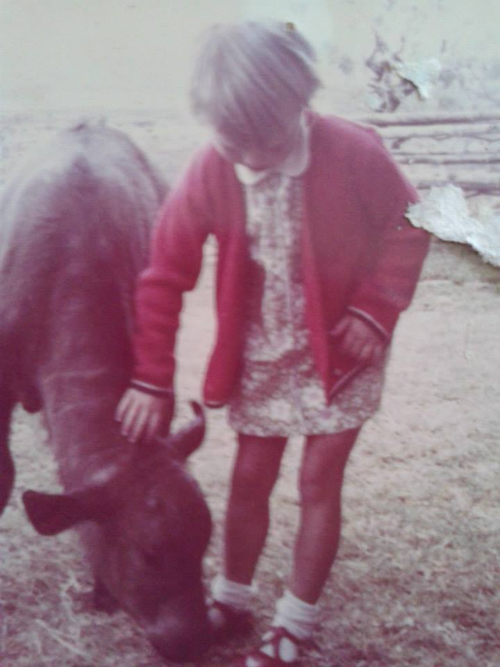 An old photograph of a young girl, around 6 years old, petting a buffalo calf.