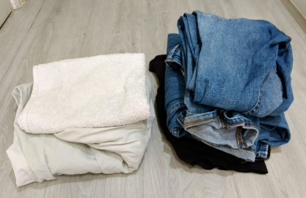 An image of two piles of washing sorted into whites and dark colours.