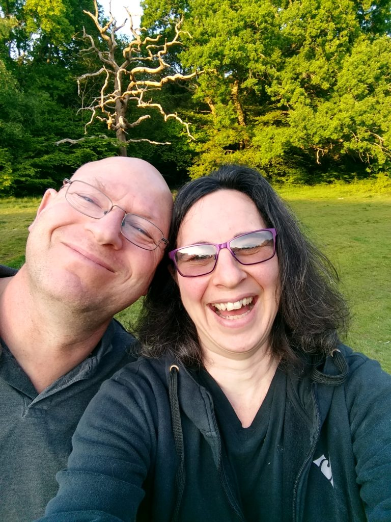 A selfie image of David and Emma Bara. There are trees in the background.