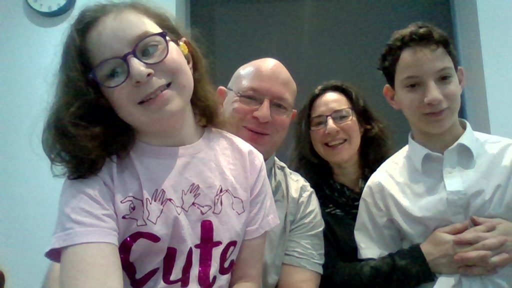 A family photo of Emma, David, Adi and Asher, sitting together in front of the computer. Adi is wearing a  shirt that says 'cute' in English and British sign language.