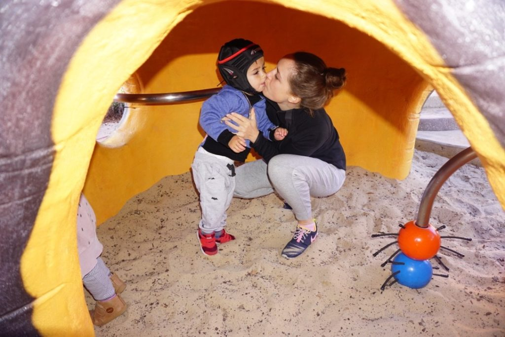 Keanu and Stacey play in a sand pit. Keanu is wearing a protective 'scrum cap  - a soft helmet which surrounds his head and fixes under his chin. Keanu is about 2 years old.
