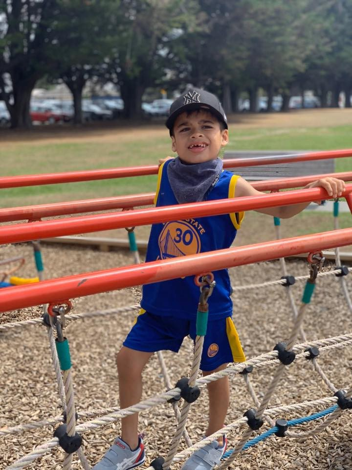 Keanu, about 6, is standing on some play equipment, smiling at the camera. He looks happy and relaxed.