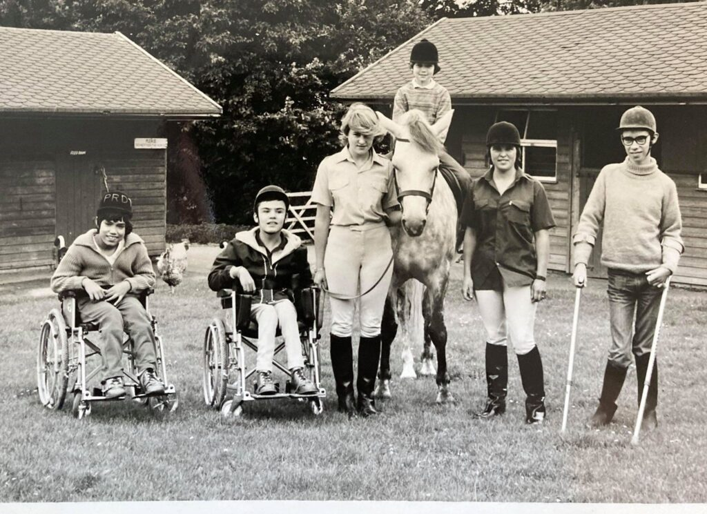 A black and white image shows 6 people and a pony standing in line. They are 4 riders and 2 members of staff.  One person is on horse back, two people are in wheelchairs, one person is using crutches. One member of staff is holding the pony's head.