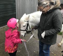 Image of a young girl moving in to kiss the forehead of a white pony. The pony is held by a volunteer.