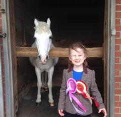 Ava, aged about 5 stands proudly in front of pony tansy's stall. Tansy is a white pony, looking straight at the camera. Ava has two, huge rosettes on her smart riding jacket.