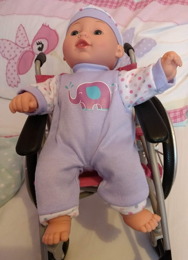 An image of a doll. The doll is sitting in a wheelchair and has 2 right feet.