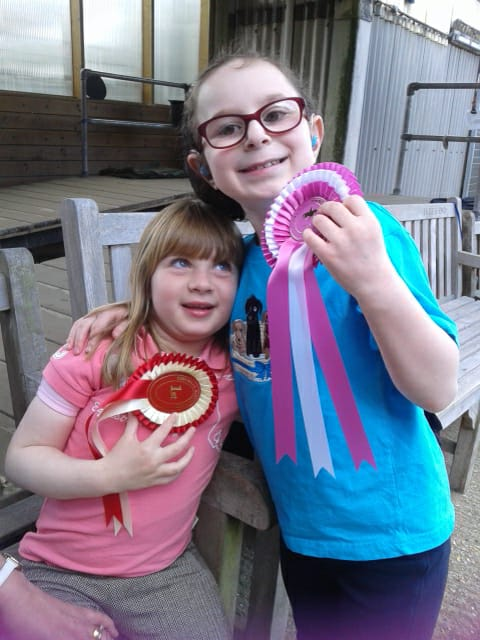 Two girls, 6 & 7, with arms round each other. Each showing off a rosette and big smiles.