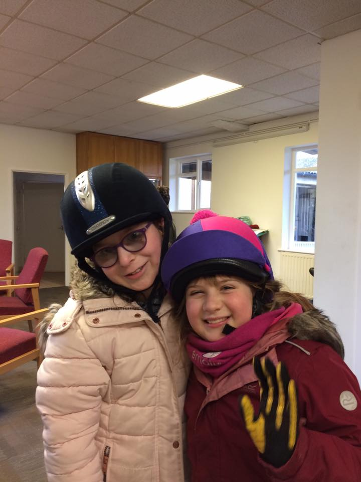 Two girls, aged 8 & 9 are posing with arms round eachother. They are both smiling and wearing riding helmets. Both are wrapped up in warm coats and scarves.