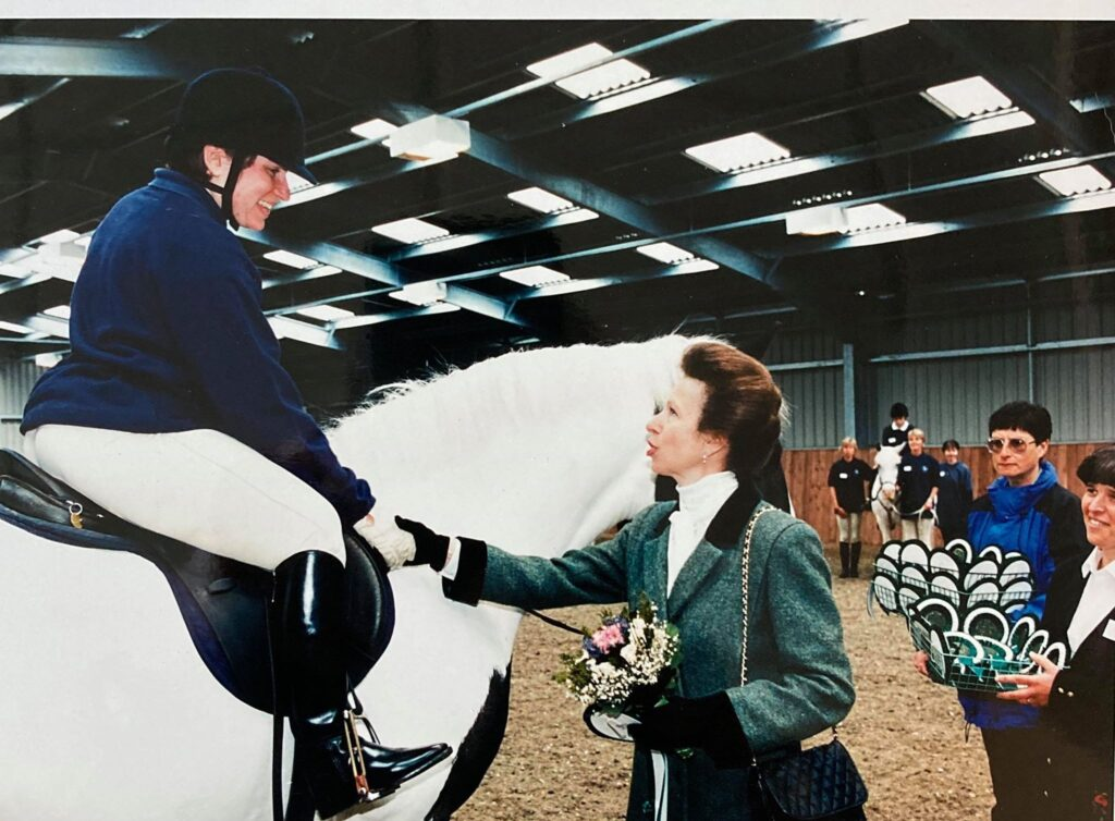 An image of Princess Anne shaking the hand of Liz Stone, equestrian paralympic medallist. Liz is sitting on the back of the pony, the Princess Royal is standing on the ground next to them.