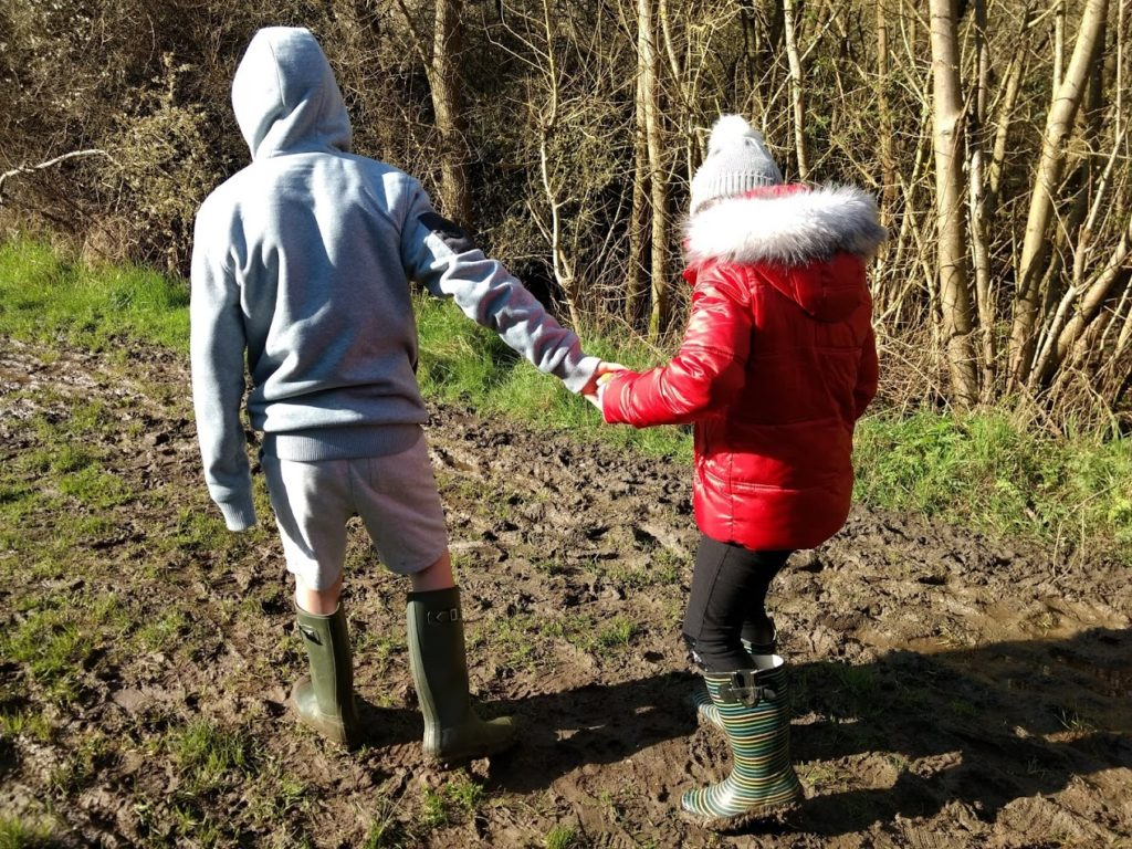 An image of 2 children walking through mud. They have their backs to the camera. The larger boy is holding his little sister's hand to help steady her.