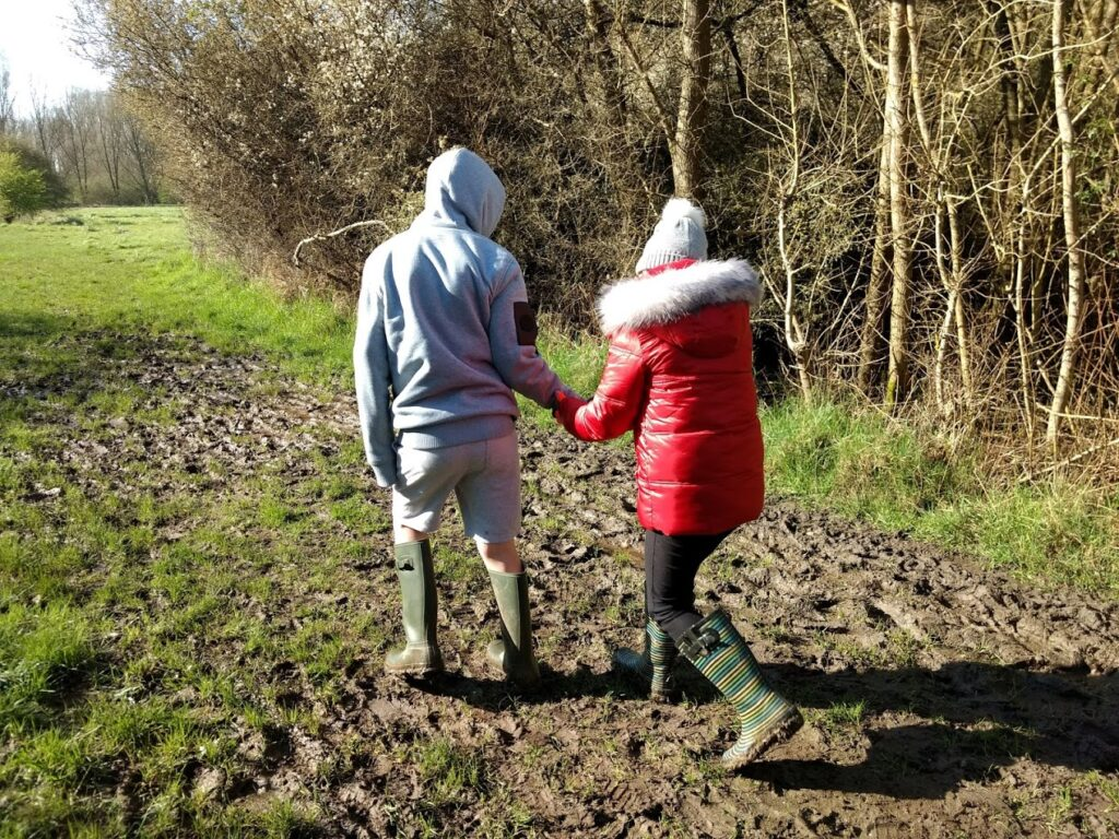 Image of a young boy and girl. The boy is helping the girl across a muddy patch in a woodland.