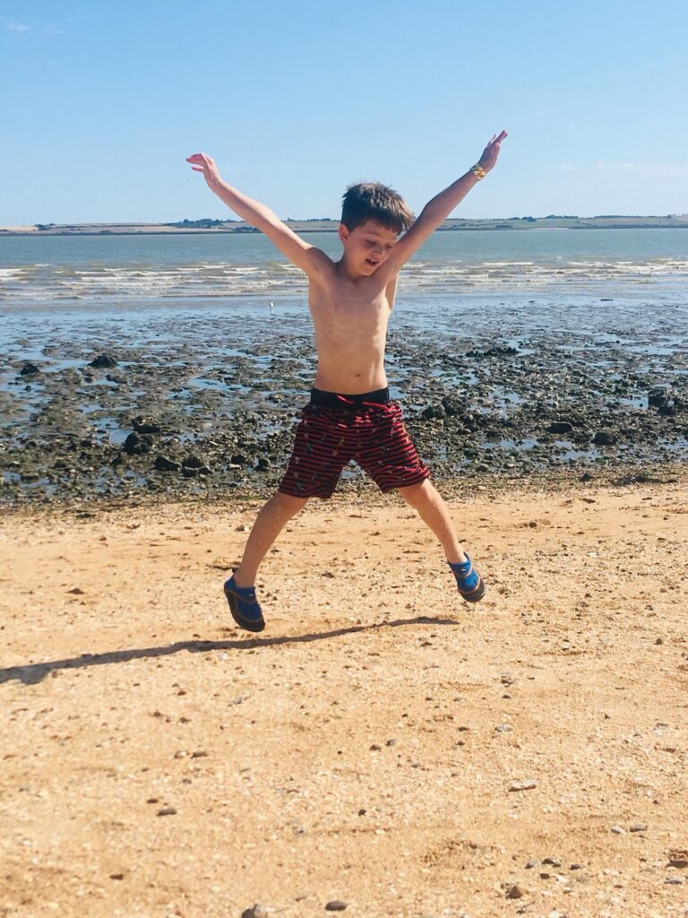 A 6 year old Alfie does a star jump on a beach.