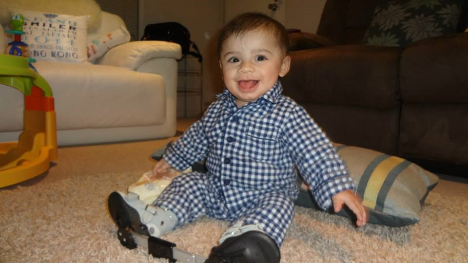 Image shows a very smiley baby Keanu, who is sitting up on his own on the floor. His feet are in boots that are connected by their heels with a flat metal bar.