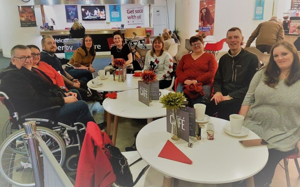 A group of 9 people, sitting together round some cafe tables and smiling for the camera. Steve Webster is among the attendees.