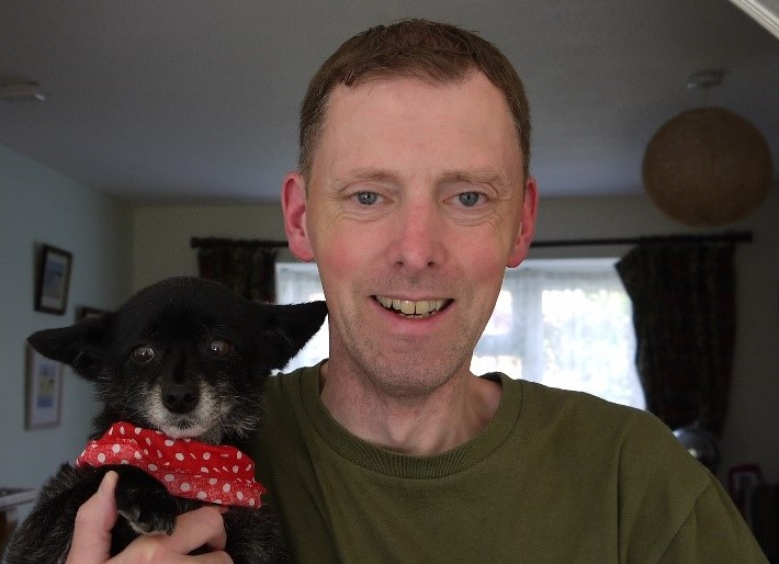 An image of Steve Webster smiling for the camera. Steve is holding a small, black dog with a red spotty scarf round its neck.
