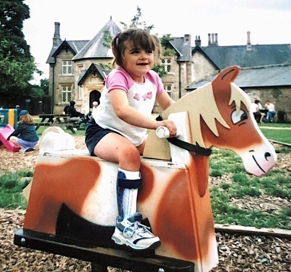 A young Charlotte (about 6) rides a toy pony in a park. She is wearing shorts and you can see her leg splint #disability #cerebralpalsy.