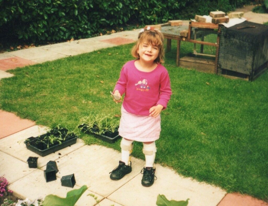 An image of a young charlotte (about 5) smiling for the camera.