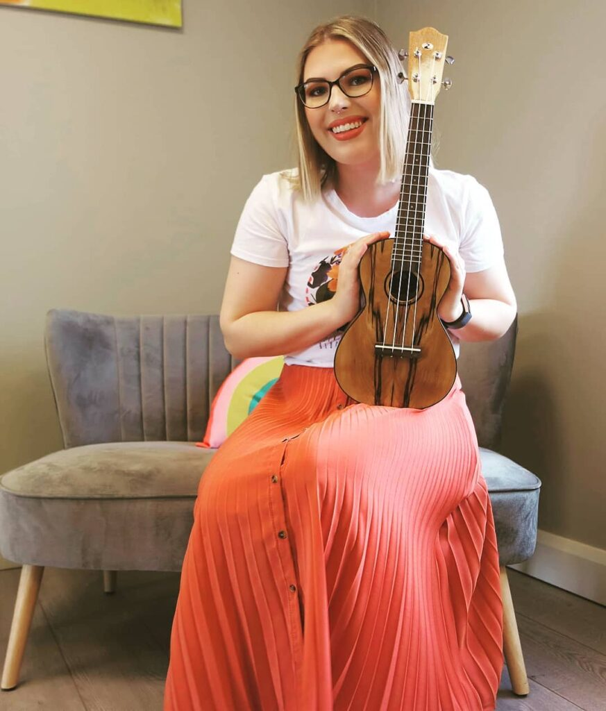 Image of Raimonda, smiling, holding a wooden ukulele.