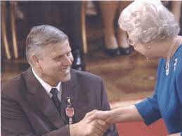 Image shows Mike receiving an honour from Queen Elizabeth.