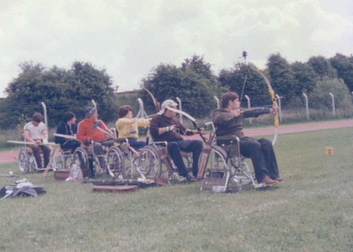 6 people in wheelchairs, lined up to compete in archery.
