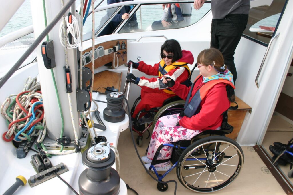 two young girls in wheelchairs, wearing life jackets are in the cockpit of a boat.
