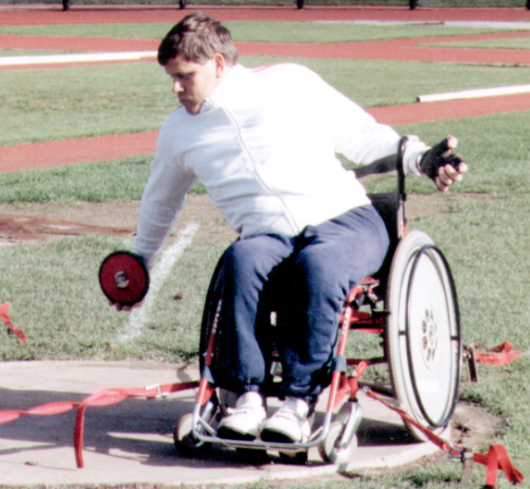 Mike Wood, in his wheelchair, holds a discus, about to take a throw.