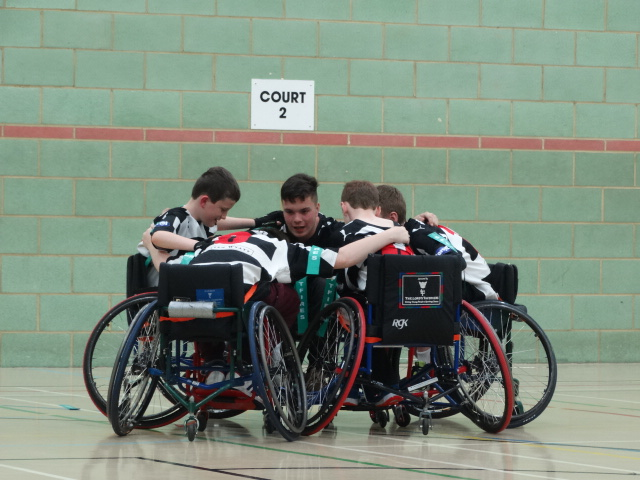 5 people in a rugby huddle, all are in wheelchairs.