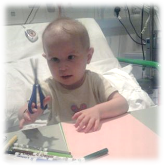 Image shows 2 year old Adi sitting in a hospital bed playing with paper and pens. She is holding a pair of scissors.