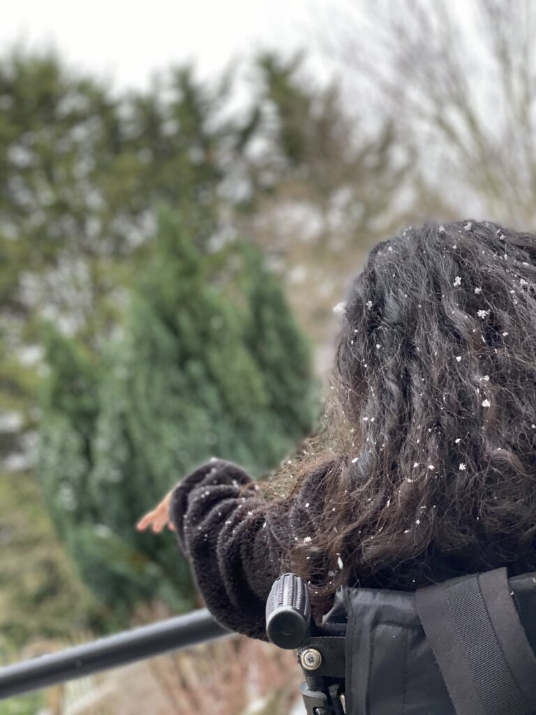 Image shows Resika from behind, sitting in her wheelchair. There is a light dusting of snow in her long dark hair.