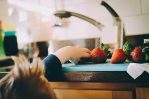 Image shows small child reaching up to a surface with strawberries on.