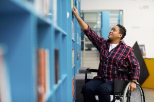 Image shows someone in a wheelchair reaching up for a book on a bookshelf.